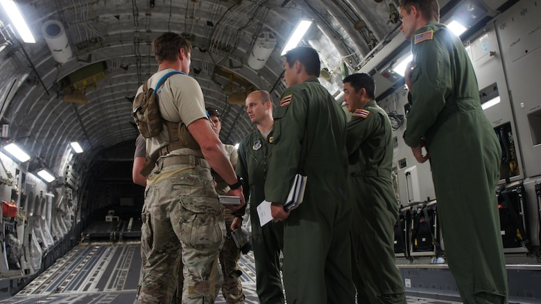Pararescue jumpers with the 31st Rescue Squadron hold a pre-mission brief with the Air Crew from the Hawaii Air National Guards 204th and the 535th Airlift Squadron before a High Altitude Low Opening air drop during Balikatan 2016, Clark Air Field, Philippines, April 15, 2016. Balikatan, which means shoulder to shoulder in Filipino, is an annual bilateral training exercise aimed at improving the ability of Philippine and U.S. military forces to work together during planning, contingency and humanitarian assistance and disaster relief operations. (U.S. Air National Guard photo by Tech. Sgt. Andrew Jackson/released)