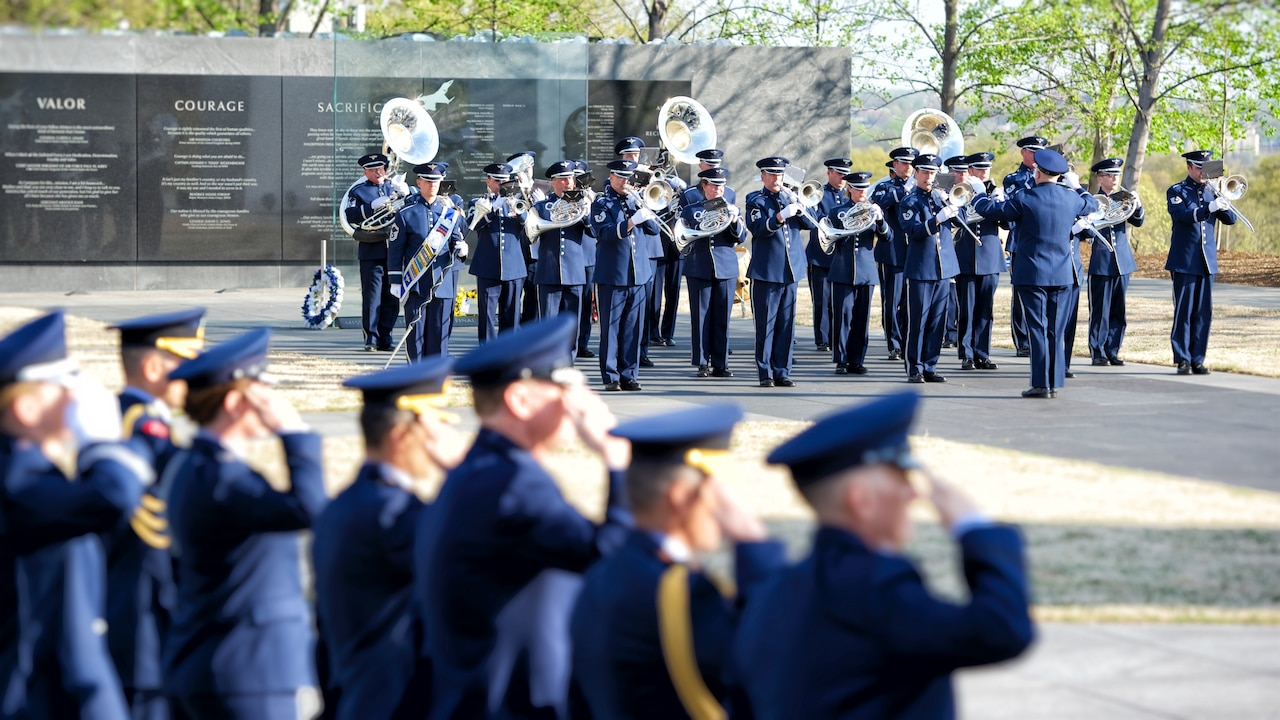 Band members dressed in military blue uniforms play horns, tubas and other instruments in front of the U.S. Air Force Memorial as other airmen salute.