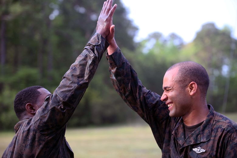A Marine and sailor with Combat Logistics Regiment 2, celebrate with a high-five after completing an endurance course at Camp Lejeune, N.C., April 22, 2016. The unit pushed through the grueling 3.4 mile course to improve their ability to work as a team and to build camaraderie.