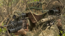 Designated marksmen with 1st Platoon, Bravo Company, 2nd Law Enforcement Battalion, look through the scope of their M110 sniper rifles while concealed in the tree line during the II Marine Expeditionary Force Command Post Exercise 3 at Marine Corps Base Camp Lejeune, North Carolina, April 20, 2016. During the CPX, 2nd LEB posted security around the campsite and defended it from mock enemies, ensuring the headquarters element could complete the mission safely.