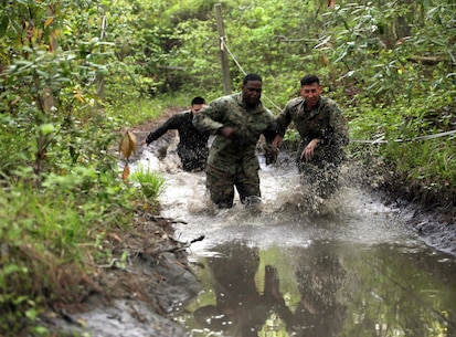 Marines with Combat Logistics Regiment 2 splash their way through one of the many mud puddles during an endurance course at Camp Lejeune, N.C., April 22, 2016. The unit pushed through the grueling 3.4 mile course to improve their ability to work as a team and to build camaraderie.