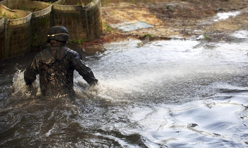 A Marine with Combat Logistics Regiment 2, makes his way through the final obstacle to exit an endurance course at Camp Lejeune, N.C., April 22, 2016. The unit pushed through the grueling 3.4 mile course to improve their ability to work as a team and to build camaraderie.