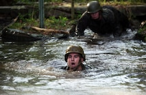 Gunnery Sgt. Joseph Janez, a career planner with Combat Logistics Regiment 2, swims through one of the deeper mud puddles during the endurance course at Camp Lejeune, N.C., April 22, 2016. The unit pushed through the grueling 3.4 mile course to improve their ability to work as a team and to build camaraderie.