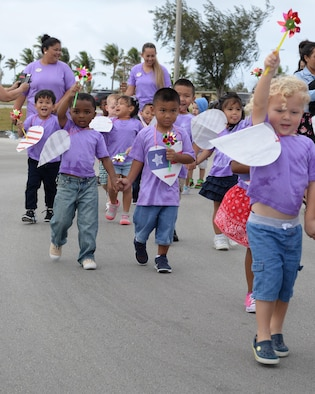 Children walk in a parade to celebrate the Month of the Military Child April 8, 2016, at Andersen Air Force Base, Guam. Throughout the week the children created themed art and designed purple shirts to signify the support of each military branch. (U.S. Air Force photo by Senior Airman Cierra Presentado/Released)