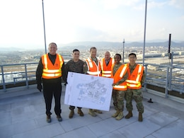 U.S. Army Corps of Engineers, Japan District Iwakuni Resident Office personnel, Marine Corps Air Station Iwakuni Marines and Command Sgt. Major Yolanda Tate pose for a photo on the roof of the control tower.