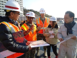Keita Tanaka, project manager, Iwakuni Resident Office, U.S. Army Corps of Engineers, Japan District holds a map of the Atago site where a housing area, sports complex and bridge are being built on Marine Corps Air Station Iwakuni, as Command Sgt. Major Yolanda Tate speaks about the magnitude of the project.