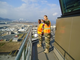 Capt. ChaTom Warren, civil engineer, Iwakuni Resident Office, U.S. Army Corps of Engineers, Japan District shows Command Sgt. Major Yolanda Tate a view of Marine Corps Air Station Iwakuni from the tallest building on base, the Air Traffic Control Tower.