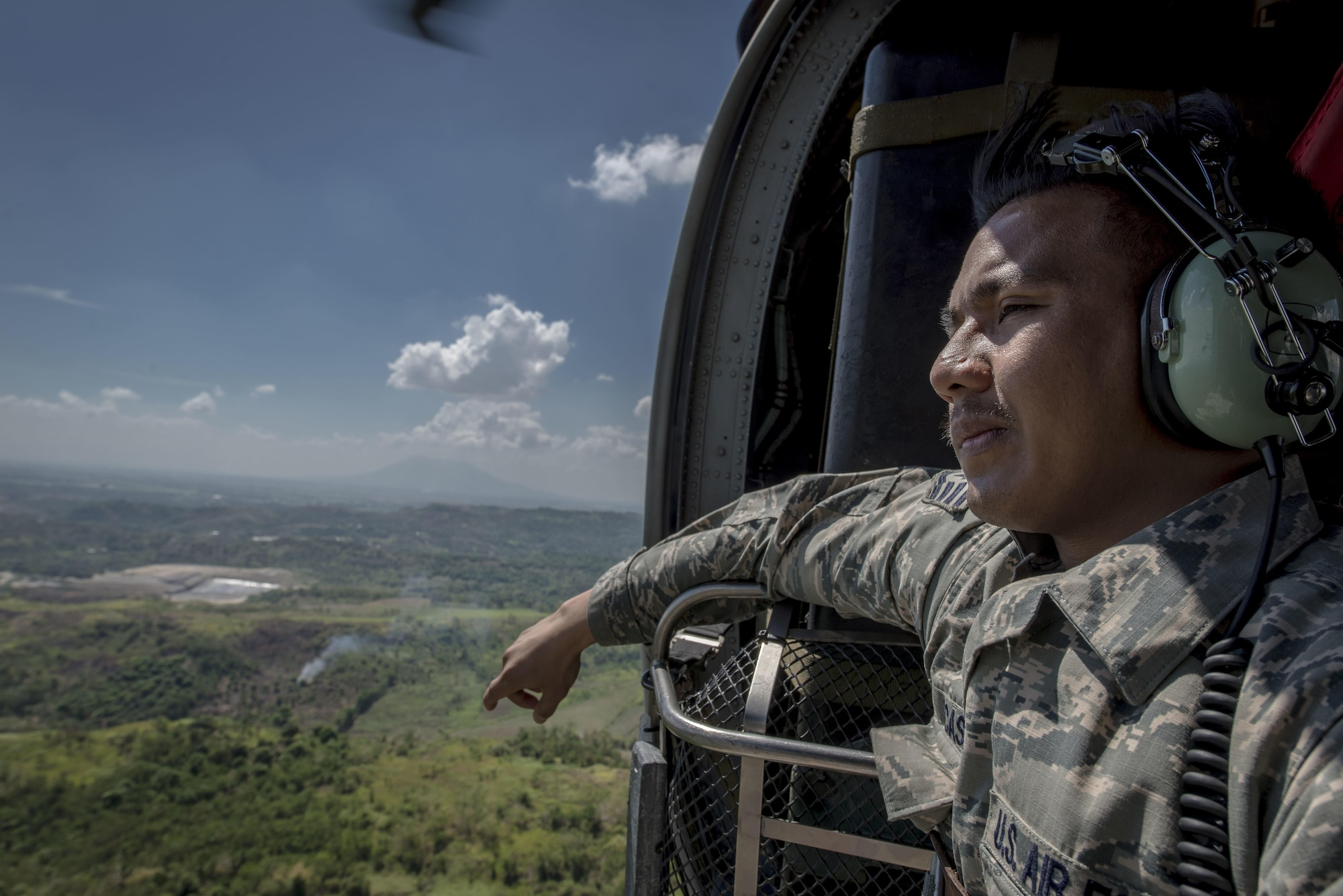 U.S. Air Force Staff Sgt. Jay Perocho Acasio, an aircrew flight equipment journeyman with the 51st Operations Support Squadron, Osan Air Base, Republic of Korea, looks out over his home country during a HH-60G Pave Hawk flight near Clark Air Base, Philippines, April 22, 2016. The staff sergeant is one of three Filipino-American Airmen serving U.S. Pacific Command's newly stood upAir Contingent in the Philippines. Acasio is from Ozamiz City in the Misamis Occidental, Philippines. (U.S. Air Force photo by Staff Sgt. Benjamin W. Stratton)