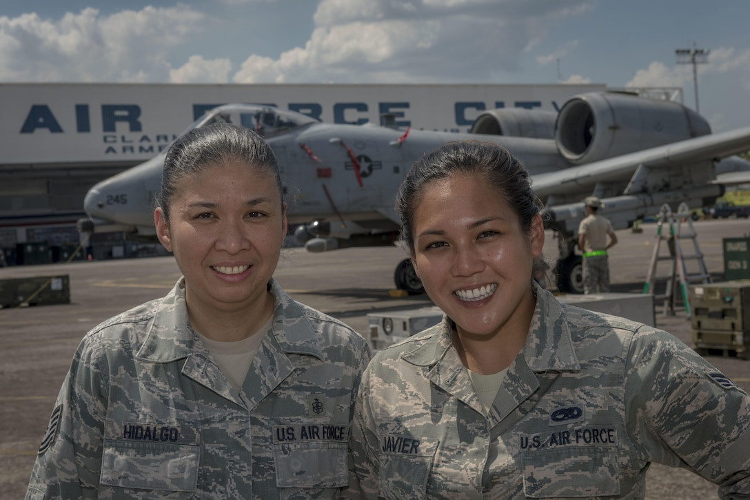 U.S. Air Force Tech. Sgt. Kathlyn Hidalgo (left), an independent duty medical technician with the 25th Fighter Squadron, and Senior Airman Nikkie Javier (right), a precision guided munitions crew chief with the 51st Munitions Squadron, both deployed from Osan Air Base, Republic of Korea, pose for a photo in front of an A-10C Thunderbolt II at Clark Air Base, Philippines, April 22, 2016. Hidalgo and Javier are two of three Filipino-American Airmen serving U.S. Pacific Command's newly stood up Air Contingent in the Philippines. Hidalgo is from Guiguinto, Bulacan, Philippines, and Javier is a Norwalk, California, native. (U.S. Air Force photo by Staff Sgt. Benjamin W. Stratton)