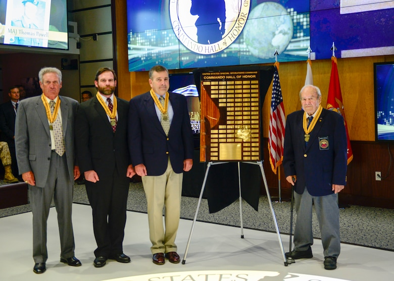 "(From left to right) Air Force Col. Billy ""Rusty"" Napier, Marine Corps Master Sgt. John Mosser, and Marine Corps Col. Robert Coates, and Army Maj. Caesar Civitella, stand next to the Commando Hall of Honor display after they were inducted into the USSOCOM Commando Hall of Honor during a ceremony held at USSOCOM headquarters, on MacDill Air Force Base, Fla., April 20. Not pictured, but inducted, is Army Maj. Thomas Powell who attended the ceremony via video teleconference. (Photo by Tech. Sgt. Angelita M. Lawrence)"