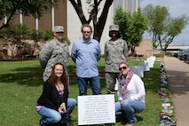 Members of the Sheppard Family Advocacy staff pose in front of a sign about child abuse and neglect at the Walk of Knowledge, an event to raise awareness for Child Abuse Prevention Month, at the Wichita County Courthouse, Wichita Falls, TX, April 15, 2016. Front Row (Left to right): Tiffany Esparza, Family Advocacy Outreach manager, Amy McGee, Family Advocacy Program and Outreach assistant. Back Row (Left to right): Capt. Jason Ross, Mental Health flight commander, Austin Solomons, Social Worker, Master Sgt. Toya Moore, Mental Health flight chief.