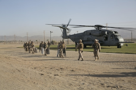 Marines with Combat Logistics Battalion 24 off load from a CH-53 'Super Stallion' at Del Valle Field aboard the Combat Center, as part of a Non-combatant Evacuation Operation exercise in support of Weapons and Tactics Instructor Course 2-16 April 15, 2016. (Official Marine Corps photo by Cpl. Thomas Mudd/Released)