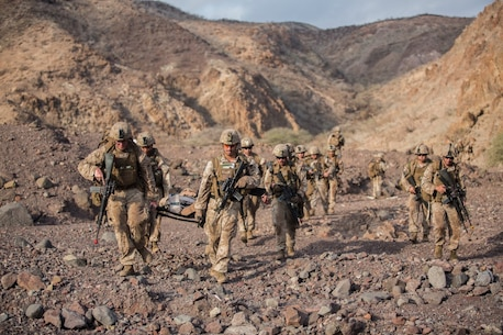 U.S. Marines and Sailors with the 13th Marine Expeditionary Unit carry a simulated injured isolated person to their extraction point during Tactical Recovery of Aircraft and Personnel training at Training Area Bravo 1, Djibouti, Africa, April 19, 2016. The 13th MEU is deployed in support of maritime security operations and theater cooperation efforts in the U.S. 5th fleet area of operations. (U.S. Marine Corps photo by Sgt. Hector de Jesus/RELEASED)