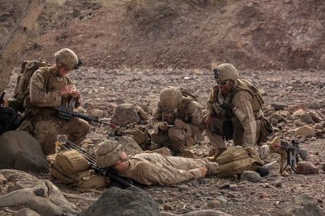 U.S. Marines and Sailors with the 13th Marine Expeditionary Unit assess a simulated injured isolated person before moving to the extraction point during Tactical Recovery of Aircraft and Personnel training at Training Area Bravo 1, Djibouti, Africa, April 19, 2016. The 13th MEU is deployed in support of maritime security operations and theater cooperation efforts in the U.S. 5th fleet area of operations. (U.S. Marine Corps photo by Sgt. Hector de Jesus/RELEASED)