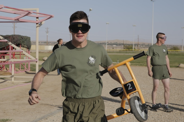 Lance Cpl. Ethan Eisenmann, tank crewman, 1st Tank Battalion, takes his turn running around the track with a tricycle while wearing beer goggles, which simulated impaired vision associated with intoxication, during the Substance Abuse Program's Scavenger Hunt at Del Valle Field April 15, 2016. (Official Marine Corps photo by Pfc. Dave Flores/Released)