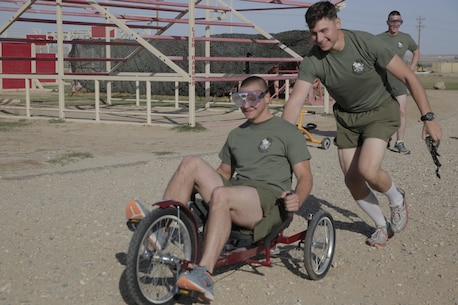 Cpl. Jimmy Carter, rifleman, 2nd Battalion, 7th Marine Regiment, pushes his teammate Pfc. James Swain, motor technician operator, 2/7, during the Substance Abuse Program's Scavenger Hunt April 15, 2016. (Official Marine Corps photo by Pfc. Dave Flores/Released)