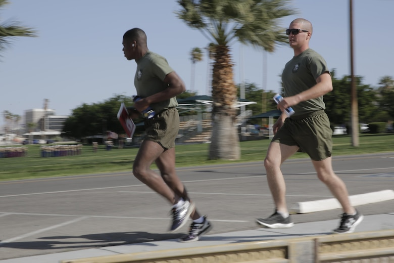 Lance Cpl. Elijah Kelly, rifleman and Lance Cpl. Abram Martin, mortar-man, 2nd Battalion, 7th Marine Regiment, run past Lance Cpl. Torrey L. Gray Field during Substance Abuse Program Scavenger Hunt April 15, 2016. (Official Marine Corps photo by Pfc. Dave Flores/Released)