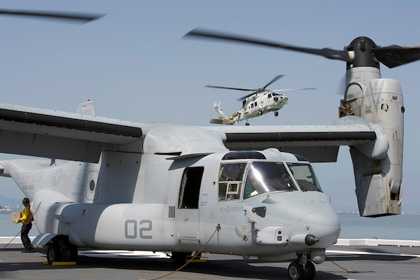 YATSUSHIRO BAY, Japan (April 22, 2016) An MV-22B Osprey from Marine Medium Tiltrotor Squadron (VMM) 265 (Reinforced) attached to the 31st Marine Expeditionary Unit is loaded with relief supplies as an SH-60K Sea Hawk helicopter from the Japan Maritime Self-Defense Force takes off from the destroyer helicopter ship JS Hyuga (DDH) 181. At request of the Japanese government, U.S. Forces Japan is providing airlift support to Japanese Self-Defense Forces (JSDF). A JSDF task force of more than 25,000 personnel is providing humanitarian and disaster relief assistance to the people affected by the magnitude 6.5 and 7.3 earthquakes that struck the Kumamoto area on 14 and 16 April 2016.