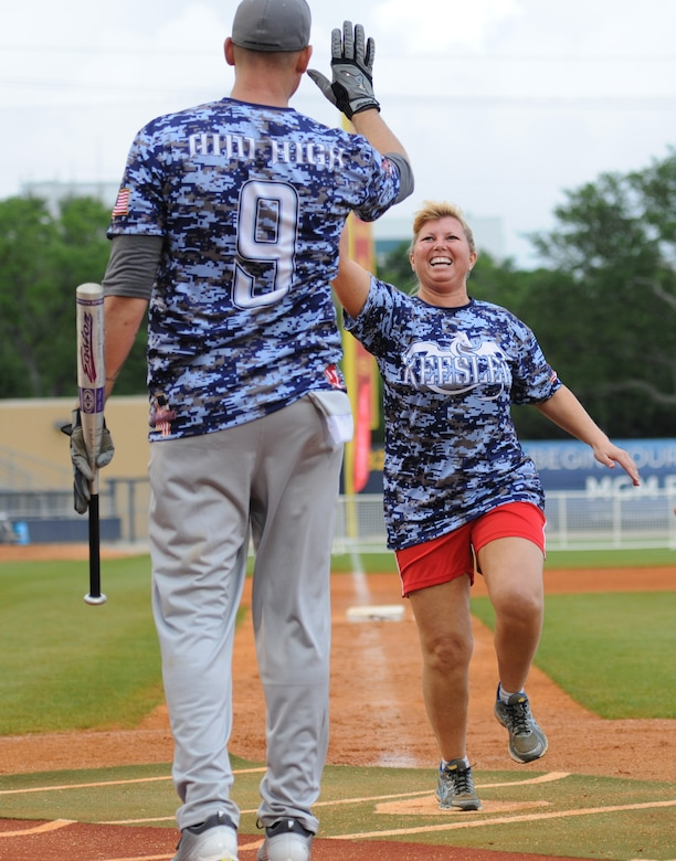 """Lt. Col. Betsy Ross, 81st Mission Support Group deputy commander and """"Boots"""" team member, gives a high-five to her teammate, Senior Master Sgt. Zackery Turbyfill, 81st Training Group military training leader superintendent, during the """"Boots versus Badges"""" softball game at the Biloxi Shuckers MGM Park April 21, 2016, Biloxi, Miss. The game was the kickoff event for the 2016 Special Olympics Mississippi Summer Games, which will be hosted by Keesler Air Force Base, Miss., May 20-21. (U.S. Air Force photo by Kemberly Groue)"""