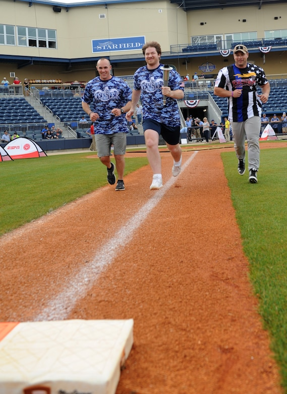 """Capt. Harlan Glinski, 81st Security Forces operations officer and """"Boots"""" team member; Lee Brown, Special Olympics athlete; and Doug DeGeorge, Biloxi Police Department police officer and """"Badges"""" team member, participate in the torch run around the baseball field during the """"Boots versus Badges"""" softball game at the Biloxi Shuckers MGM Park April 21, 2016, Biloxi, Miss. The game was the kickoff event for the 2016 Special Olympics Mississippi Summer Games, which will be hosted by Keesler Air Force Base, Miss., May 20-21. (U.S. Air Force photo by Kemberly Groue)"""