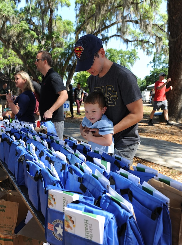 Tech. Sgt. Albert Cortez, 81st Diagnostic and Therapeutics Squadron radiology technician, helps his son, Alex, grab a goody bag during Child Pride Day at marina park April 23, 2016, Keesler Air Force Base, Miss. Keesler families attended the annual event which featured activities, demonstrations and information on programs focused on care of military families. Child Pride Day was held in conjunction with the month of the military child. (U.S. Air Force photo by Kemberly Groue)