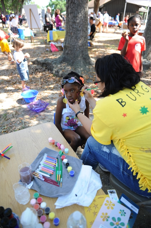 Alesiya Blockett, daughter of U.S. Marine Corps Staff Sgt. Alonzo Blockett, Keesler Marine Detachment instructor, gets her face painted by Angela Burgos, Keesler Family Child Care provider, during Child Pride Day at marina park April 23, 2016, Keesler Air Force Base, Miss. Keesler families attended the annual event which featured activities, demonstrations and information on programs focused on care of military families. Child Pride Day was held in conjunction with the month of the military child. (U.S. Air Force photo by Kemberly Groue)