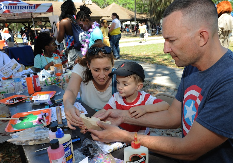 Lt. Col. Douglas Fowler, 338th Training Squadron commander, and his wife, Meri Mengo, assist their son, Andrew, with building a wooden race car during Child Pride Day at marina park April 23, 2016, Keesler Air Force Base, Miss. Keesler families attended the annual event which featured activities, demonstrations and information on programs focused on care of military families. Child Pride Day was held in conjunction with the month of the military child. (U.S. Air Force photo by Kemberly Groue)