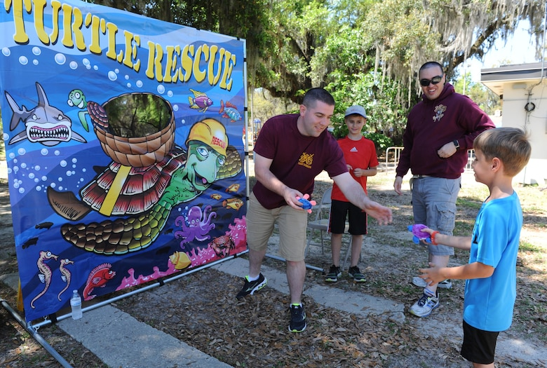 """Airman 1st Class Daniel Shanks, 338th Training Squadron, assists Zachary Smith, son of Master Sgt. Sarah Smith, 81st Training Support Squadron curriculum developer, with a game of """"Turtle Rescue"""" during Child Pride Day at marina park April 23, 2016, Keesler Air Force Base, Miss. Keesler families attended the annual event which featured activities, demonstrations and information on programs focused on care of military families. Child Pride Day was held in conjunction with the month of the military child. (U.S. Air Force photo by Kemberly Groue)"""