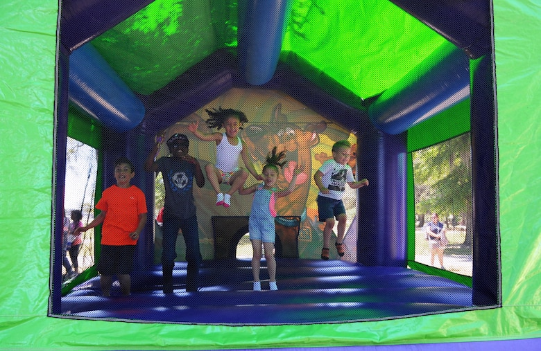 A group of children jump inside a bouncy house during Child Pride Day at marina park April 23, 2016, Keesler Air Force Base, Miss. Keesler families attended the annual event which featured activities, demonstrations and information on programs focused on care of military families. Child Pride Day was held in conjunction with the month of the military child. (U.S. Air Force photo by Kemberly Groue)