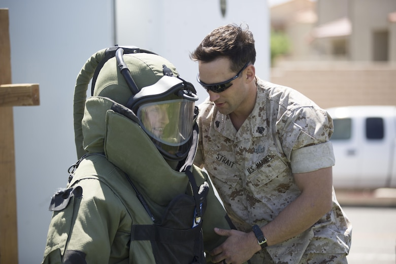 Sgt. Alexander Strait, Explosive Ordnance Disposal technician, EOD, helps Tatum Genovese, 14, try on a bomb disposal suit during the Twentynine Palms Car Show and Street Fair at Luckie Park in Twentynine Palms, Calif., April 16, 2016. (Official Marine Corps photo by Cpl. Julio McGraw/Released)