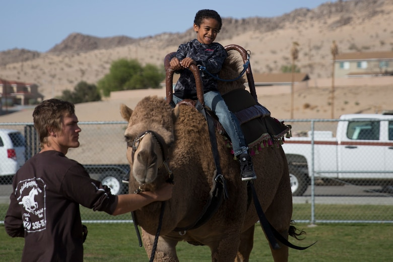 Mikey Feliciano, son of Staff Sgt. Anthony Feliciano, imagery analyst, Unmanned Vehicle Aerial Squadron 1, rides a camel during the Earth Day Extravaganza aboard at Lincoln Military Housing Athletic Field April 15, 2016. (Official Marine Corps photo by Cpl. Connor Hancock/Released)