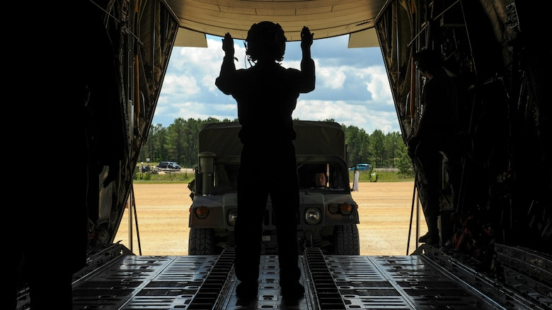 Royal Australian Air Force Sgt. Paul Cox, No. 37 Squadron C-130J loadmaster, directs a U.S. Air Force Humvee onto a C-130J April 22, 2016, at an improvised landing zone on Fort Polk, La. Australian forces worked alongside coalition forces from the U.S., Sweden, New Zealand and Australia during the Green Flag Little Rock 16-06 exercise. (U.S. Air Force photo/ Senior Airman Harry Brexel)