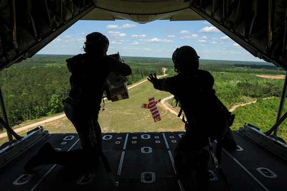 From left, Royal Australian Air Force Warrant Officer Ryan Bowden, and Royal Australian Air Force Sgt. Paul Cox, No. 37 Squadron C-130J loadmasters, drop two heliboxes from the back of a C-130J April 22, 2016, over Fort Polk, La. The Australian Airmen trained with U.S. Air Force Airmen from Little Rock Air Force Base, Ark., as part of Green Flag 16-06, a large-scale, joint mobility exercise. (U.S. Air Force photo/ Senior Airman Harry Brexel)