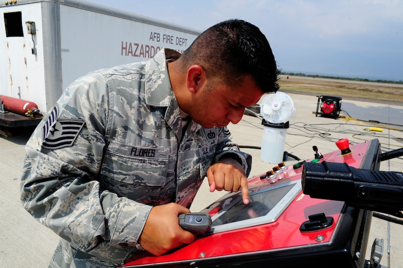 """U.S. Air Force Tech. Sgt. Joseph Flores, 612th Air Base Squadron, ensures the live-fire trainer is fully operational during fire extinguishing training during a CENTAM SMOKE (Sharing Mutual Operational Knowledge and Experience) exercise at Soto Cano Air Base, Honduras, April 20, 2016.  During the week-long event, the 34 participants combine classroom lessons with scenarios in the field, using structural, automobile and aircraft live fires, first response medical procedures, patient loading for medical evacuations, familiarization with personal protective gear and using the """"Jaws of Life"""" extraction tool. (U.S. Army photo by Martin Chahin/Released)"""