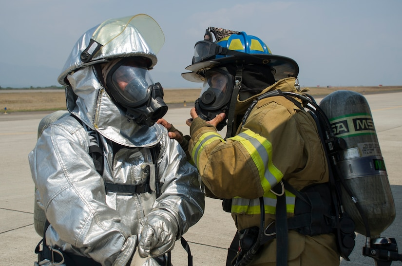 "Herberth Gaekel, 612th Air Base Squadron fire inspector, verifies the correct wear of protective gear by one of 34 Central American participants during CENTAM SMOKE (Sharing Mutual Operational Knowledge and Experience), a biannual exercise hosted at Soto Cano Air Base, Honduras, April 19, 2016. During the week-long event, participants combine classroom lessons with scenarios in the field, using structural, automobile and aircraft fires, first response medical procedures, patient loading for medical evacuations, familiarization with personal protective gear, and using the ""Jaws of Life"" extraction tool. Some firefighters in attendance, and other from previous iterations, helped fight the recent fires near Tela, Honduras. (U.S. Air Force Photo by Capt. David Liapis/Released)"
