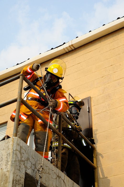 """Costa Rican firefighter Antonio Perez (left) and Panamanian firefighter Katheryn Bravo complete an obstacle climb, one of the many challenges faced during CENTAM SMOKE (Sharing Mutual Operational Knowledge and Experience), a biannual exercise hosted at Soto Cano Air Base, Honduras, April 19, 2016. During the week-long event, participants combine classroom lessons with scenarios in the field, using structural, automobile and aircraft fires, first response medical procedures, patient loading for medical evacuations, familiarization with personal protective gear, and using the """"Jaws of Life"""" extraction tool. (U.S. Army photo by Martin Chahin/Released)"""