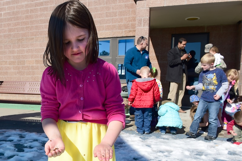A girl from the Crested Butte Child Development Center stands with a handful of ladybugs April 22, 2016, on Buckley Air Force Base, Colo. Team Buckley honored Earth Day with the release of ladybugs and a tree planting ceremony. (U.S. Air Force photo by Airman 1st Class Luke W. Nowakowski/Released)