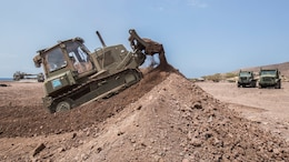 U.S. Marine Lance Cpl. Nicholas Bouvia, a heavy equipment operator with the 13th Marine Expeditionary Unit, builds a berm for security in Djibouti, Apr. 9, 2016. The 13th MEU is conducting sustainment training to maintain proficiency and combat readiness while deployed with the Boxer Amphibious Ready Group during Western Pacific Deployment 16-1.