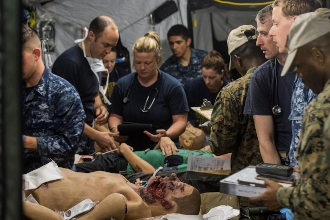 Sailors with 2nd Medical Battalion address simulated trauma victims during the final scenario of Health Service Augmentation Program training at Camp Lejeune, N.C., April 22, 2016. HSAP training, a week-long field exercise, is geared towards training medical personnel to function in a shock trauma platoon in a deployed environment.