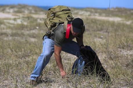 Gunnery Sgt. Bernard Snyder picks up pieces of trash with Marines from 2nd Radio Battalion and 2nd Law Enforcement Battalion to clean up Shackleford Banks Island on April 21, 2016. Snyder said he visited the island on his free time and noticed an opportunity to help better the island through community service. (U.S. Marine Corps photo by Lance Cpl. Miranda Faughn/Released)