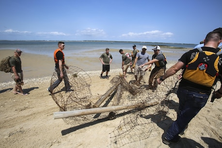 Clearing debris from the beach, Marines from 2nd Radio Battalion and 2nd Law Enforcement Battalion drag a fence to a ferry for removal as part of a beach clean-up of Shackleford Banks Island April 21, 2016. The Marines worked in cooperation with the Single Marine Program for transportation and the National Park service for removal of the trash. (U.S. Marine Corps photo by Lance Cpl. Miranda Faughn/Released)