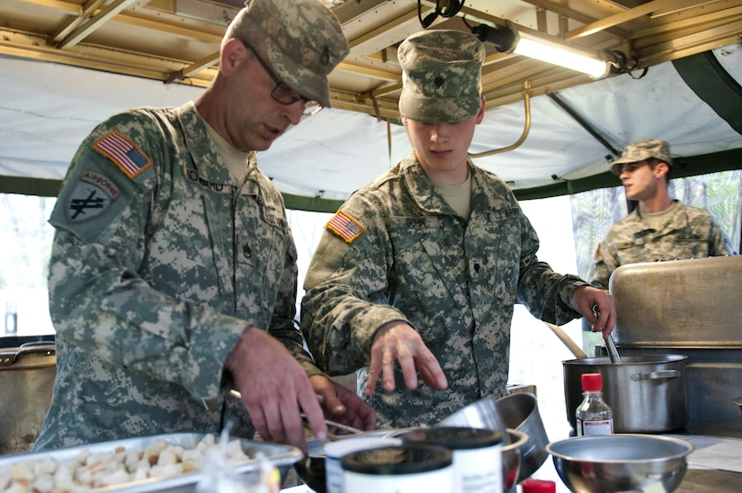 Spc. Austin Gohn, a food service specialist with the 733rd Transportation Company, middle, instructs Staff Sgt. Dan Howard, also with 733rd T.C., on what utensils to bring him during the annual Philip A. Connelly Award competition at Fort Indiantown Gap, Pa., April 23, 2016. (U.S. Army photo by Staff Sgt. Dalton Smith / Released)