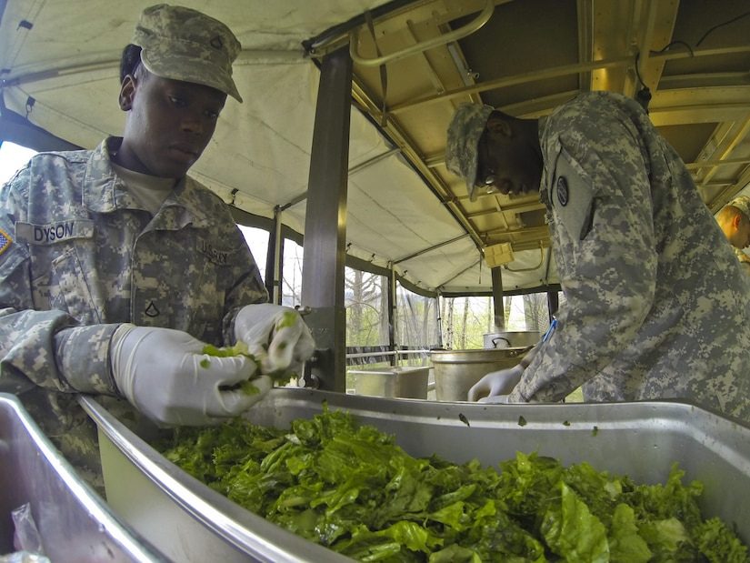 Pvt. 1st. Class Victoria Dyson, with the 733rd Transportation Company, left, prepares a salad for the annual Philip A. Connelly Award competition at Fort Indiantown Gap, Pa., April 23, 2016. (U.S. Army photo by Staff Sgt. Dalton Smith / Released)