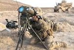 Army Sgt. Daniel Hoffman, a fire support noncommissioned officer with Delta Company, 1st Battalion, 12th Infantry Regiment, 4th Inf. Brigade Combat Team, 4th Inf. Division, looks through a battery-powered long-distance laser rangefinder to get measurments for an upcoming artillery shoot south of Kandahar Airfield, Afghanistan.
