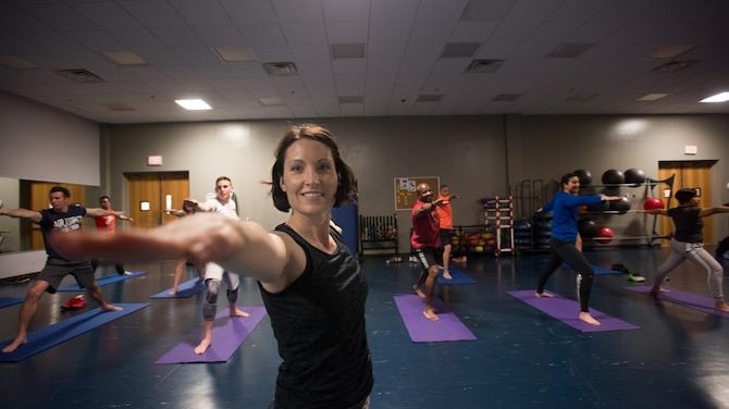Lt. Col. Janelle Macaulay, the 305th Operations Support Squadron commander, leads members of her unit in a yoga class April 19, 2016, at the Falcon Fitness Center at Joint Base McGuire-Dix-Lakehurst, N.J. Yoga is one of several mental and physical fitness initiatives Macaulay and her leadership have implemented in the squadron. (U.S. Air Force photo/Staff Sgt. Katherine Tereyama)