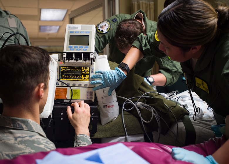 Members of the 59th Medical Wing Extracorporeal Membrane Oxygenation and Critical Care Air Transport Team adjust settings on a vital signs monitor at Lafayette General Medical Center April 20. The teams were preparing the patient for transport to San Antonio Military Medical Center, Joint Base San Antonio-Fort Sam Houston, Texas. (U.S. Air Force photo/Staff Sgt. Kevin Iinuma)
