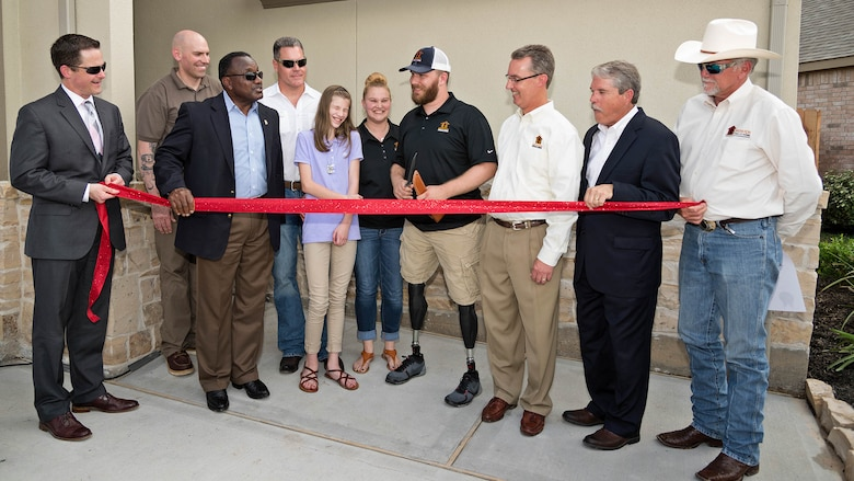 U.S. Marine Corps Cpl. Jonathan Dowdell (center), holds a combat knife in his hands to begin the ribbon cutting ceremony as part of a special welcome home ceremony in League City, Texas, April 14, 2016. The home dedication marks Operation FINALLY HOME's 100th dedication for a deserving veteran or surviving spouse.
