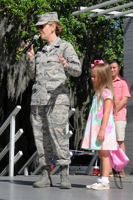 Col. Michele Edmondson, 81st Training Wing commander, delivers opening remarks with her daughter, Jacqueline McGowan, during Child Pride Day at marina park April 23, 2016, Keesler Air Force Base, Miss. Keesler families attended the annual event which featured activities, demonstrations and information on programs focused on care of military families. Child Pride Day was held in conjunction with the month of the military child. (U.S. Air Force photo by Kemberly Groue)