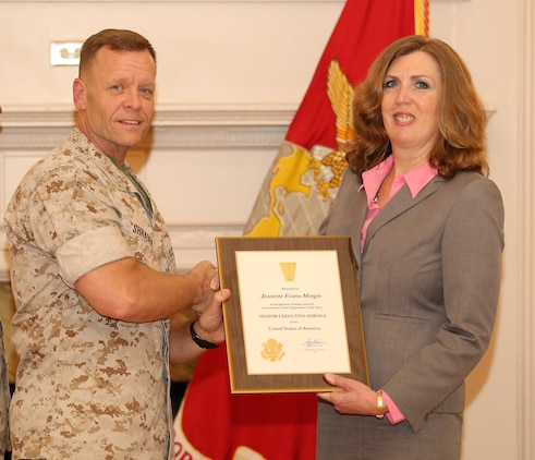 Brig. Gen. Joseph Shrader, commander of Marine Corps Systems Command, presents a certificate to Jeannette Evans-Morgis during her Senior Executive Service Appointment Ceremony April 21 at Harry Lee Hall aboard Marine Corps Base Quantico, Virginia. Upon her selection to the SES in December 2015, Evans-Morgis assumed responsibility as chief engineer of the Marine Corps and deputy commander for Systems Engineering, Interoperability, Architectures and Technology at Marine Corps Systems Command. (U.S. Marine Corps photo by Mathuel Browne)