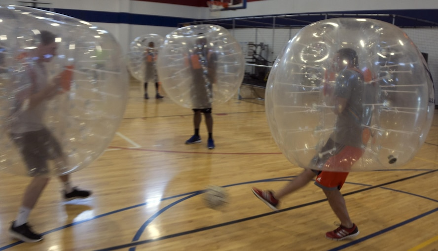 An Airman attempts to kick a soccer ball past a defender April 22, 2016, during a bubble soccer game in the Freedom Hall Fitness Center on F.E. Warren Air Force Base, Wyo. Six Teams competed in 5-minute games. (U.S. Air Force photo by Senior Airman Brandon Valle)